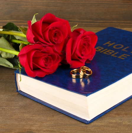 Wedding rings on bible with roses on wooden background