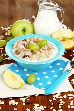 eating right: Useful oatmeal in bowl with fruit on wooden table close-up Stock Photo