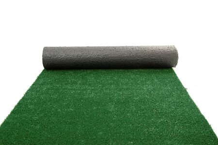 Artificial rolled green grass isolated on white photo