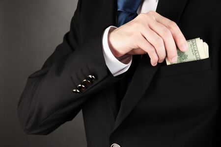 cash money: Hombre de negocios que esconder dinero en el bolsillo en el fondo negro