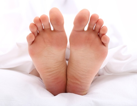 Beautiful feet of a young woman lying in bed close up photo