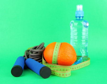 Orange with measuring tape,skipping rope and bottle of water, on color background Stock Photo - 18629972