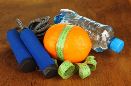 Orange with measuring tape,skipping rope and bottle of water, on wooden background photo