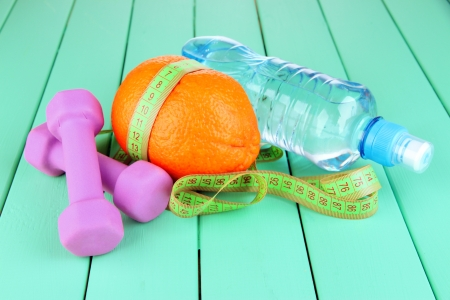 Orange with measuring tape, dumbbells and bottle of water, on color wooden background Stock Photo - 18630563
