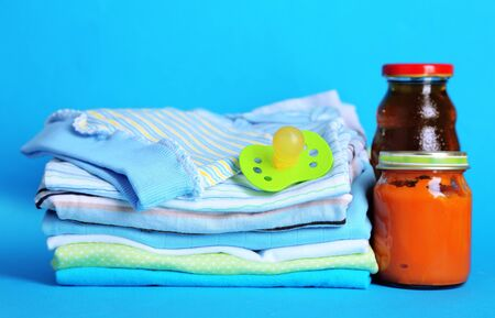 Pile of baby clothes on blue background photo