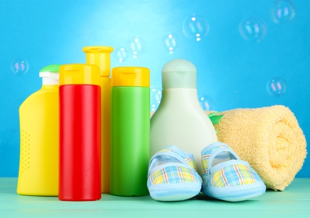 Baby cosmetics, towel and boots on wooden table, on blue background photo