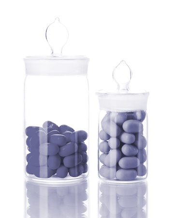 linctus: Transparent bottles with pills in grey light isolated on white Stock Photo