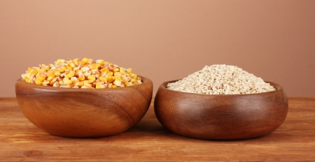 Raw corn and wheat in wooden bowls on table on brown background photo