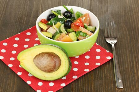 Tasty avocado salad in bowl  on wooden table close-up photo