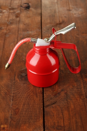 lubricator: Red oil can, on wooden background Stock Photo