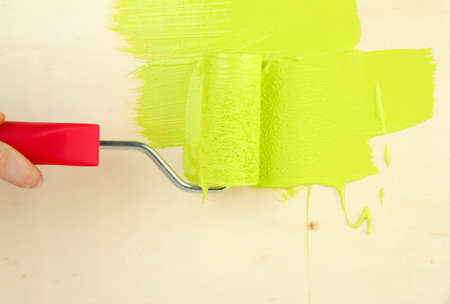 Paint roller brush with green paint, on wooden background Stock Photo - 18609333