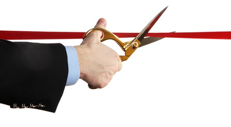 establish: Mans hand cutting red ribbon with pair of scissors isolated on white Stock Photo