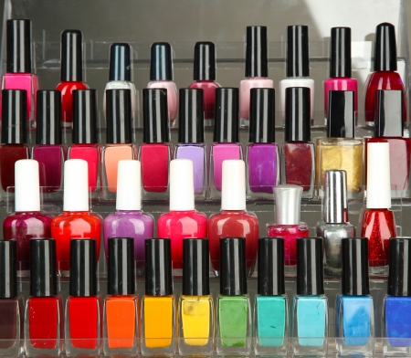 Bright nail polishes on shelf on grey background photo