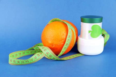Orange with measuring tape and body cream, on color background Stock Photo - 18610334