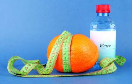 Orange with measuring tape, bottle of water, on color background Stock Photo - 18609917