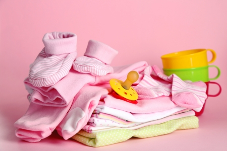 pile of clothes: Pile of baby clothes on pink background