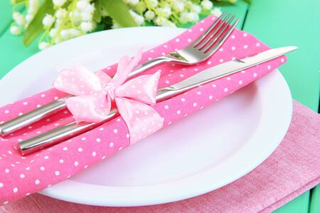 Table setting in white and pink tones on color  wooden background Stock Photo - 18610089