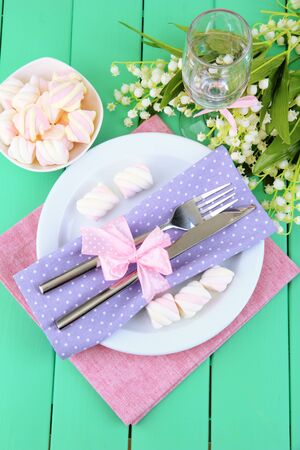 Table setting in violet and pink tones on color  wooden background Stock Photo - 18610624