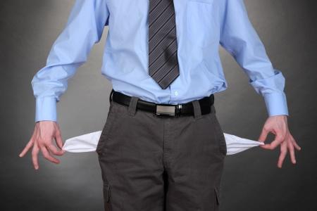 bolsillos vacios: Hombre de negocios que muestra los bolsillos vac�os, sobre fondo gris Foto de archivo