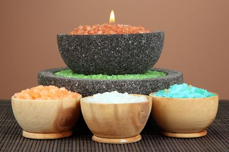 cosmetic products: Candle in stone bowl with marine salt, on bamboo mat, on brown background