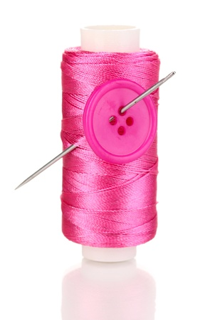 Pink bobbin with needle and buttons isolated on white photo