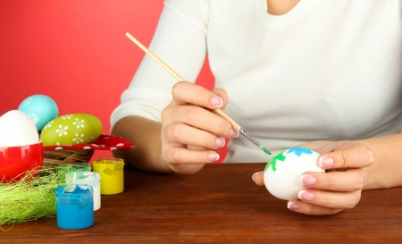 Young woman painting Easter eggs, on color background Stock Photo - 18642419