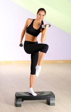 Young woman doing fitness exercises on stepper at gymnasium photo