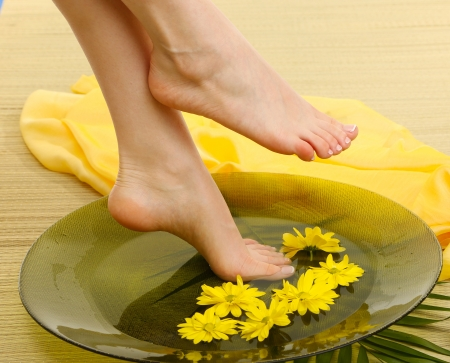 Female feet in spa bowl with water, on bamboo mat photo