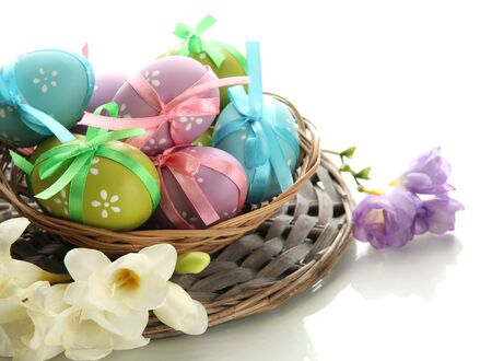 Bright easter eggs with bows in basket, isolated on white photo