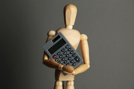 Wooden mannequin with calculator on grey background Stock Photo - 18642517