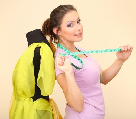 Beautiful young dressmaker in workroom photo