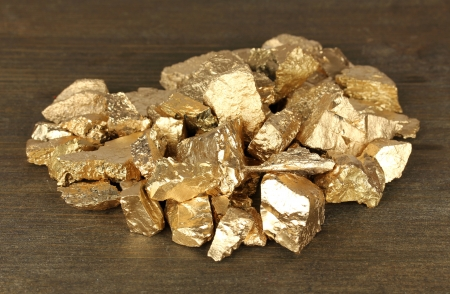 tough luck: Golden nuggets on wooden background