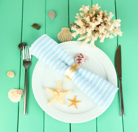 Marine table setting on color wooden background photo