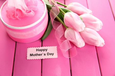 Beautiful bouquet of tulips and gift for Mothers Day on pink wooden background photo