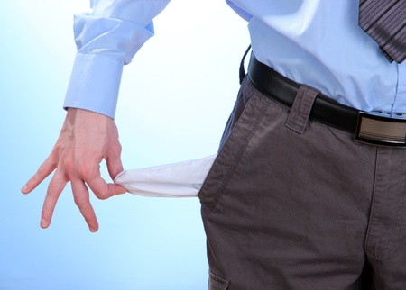Business man showing his empty pocket, on blue background photo
