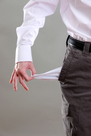 Business man showing his empty pocket, on grey background photo