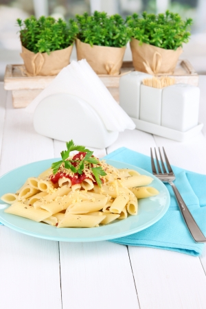 Rigatoni pasta dish with tomato sauce on white wooden table in cafe photo