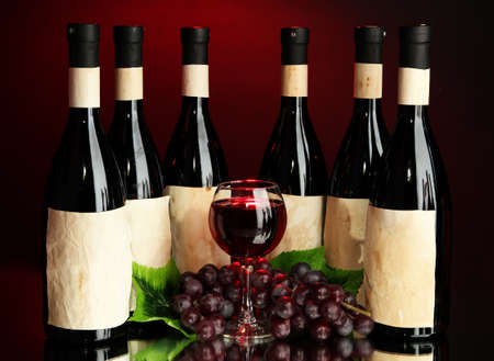 Composition of wine bottles, glass and  grape, on dark red background photo
