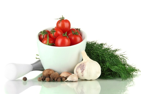 Composition of mortar, spices, tomatoes and  green herbs, isolated on white photo