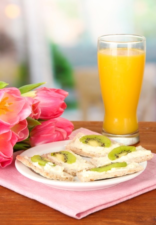 Tasty canapes with cheese and kiwi, on color plate, on bright background photo