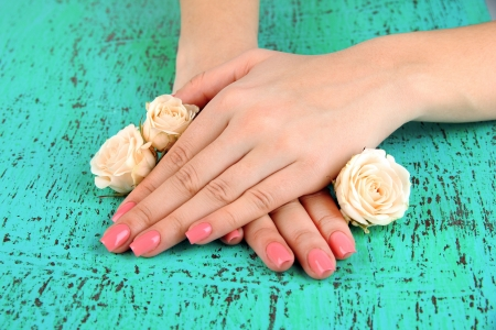 nail lacquer: Woman hands with pink manicure and flowers, on color background Stock Photo