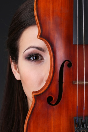Beautiful young girl with violin on grey background photo