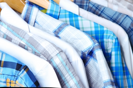 Mens shirts on hangers on wooden background photo