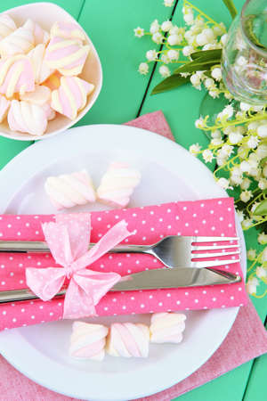 Table setting in white and pink tones on color  wooden background photo