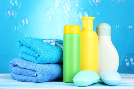 Baby cosmetics, towels and soap on wooden table, on blue background photo