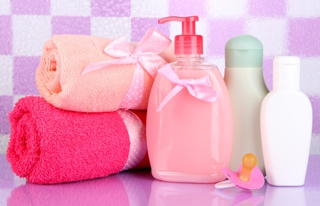 Baby cosmetics and towels  in bathroom on violet tile wall background Stock Photo - 18695802