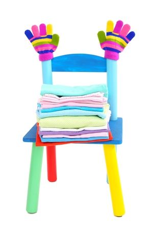 Small and colorful chair with baby clothes isolated on white Stock Photo - 18693919
