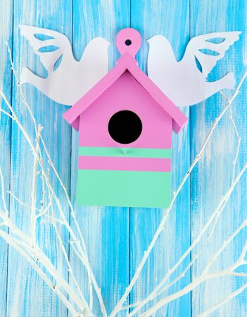 Decorative nesting box with paper birds and color branches, on color wooden  background photo