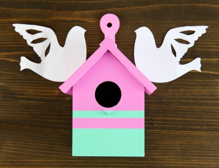 Decorative nesting box with paper birds, on wooden  background photo