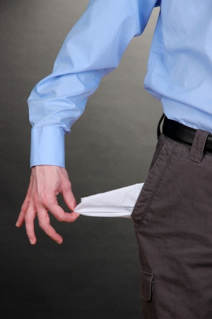 empty pocket: Business man showing his empty pocket, on grey background